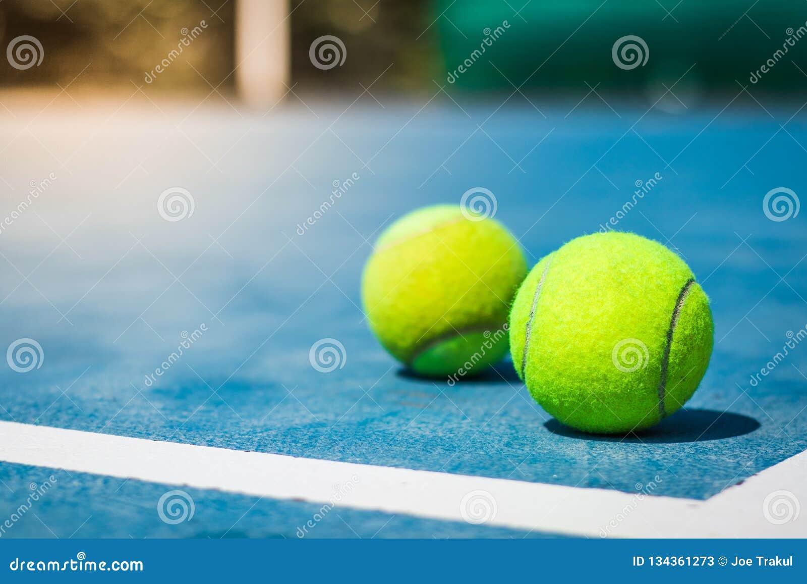 Tennisballen voor het gerecht op hoek blauwe vloer