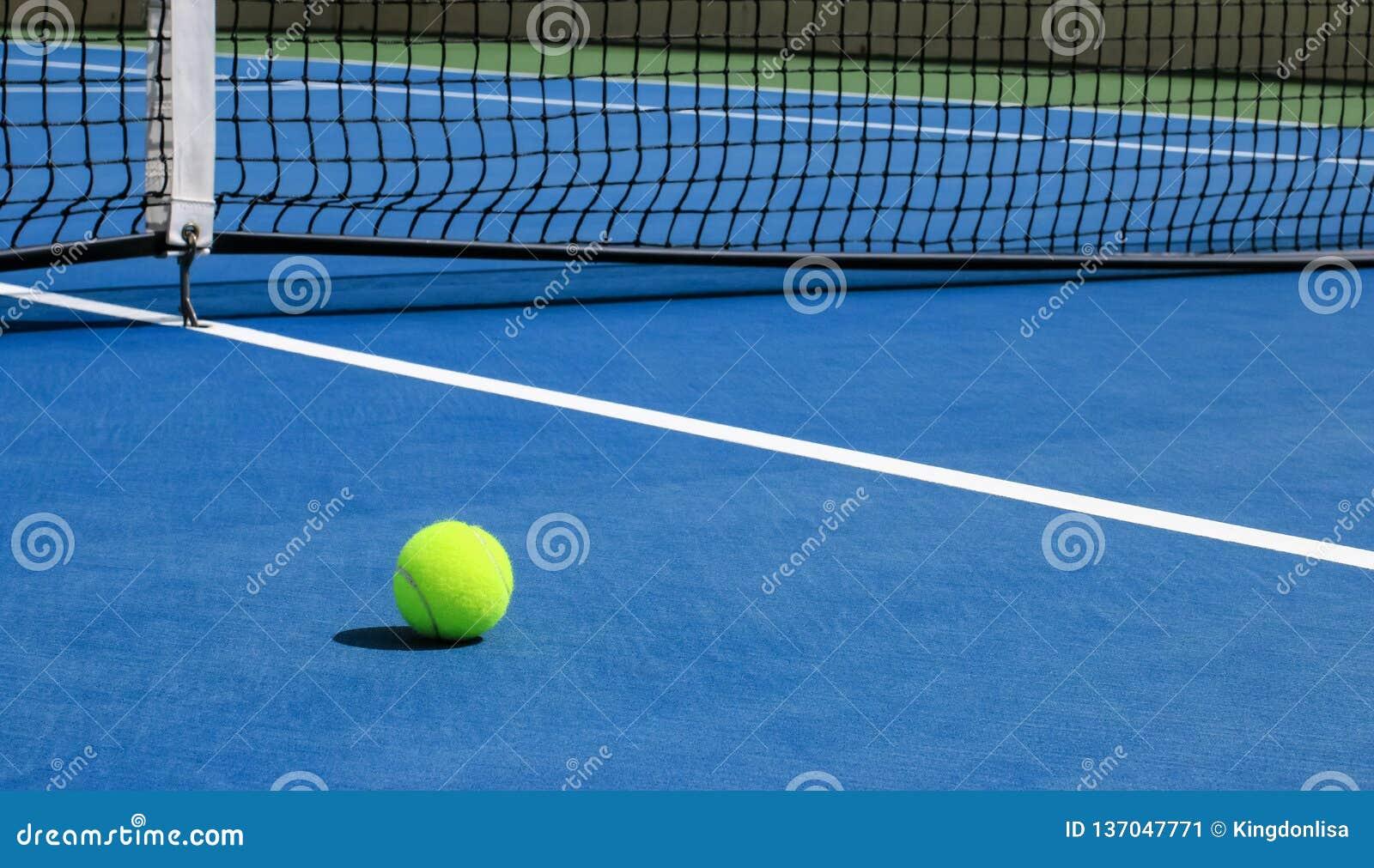 Tennisboll på den blåa domstolen med netto i bakgrund