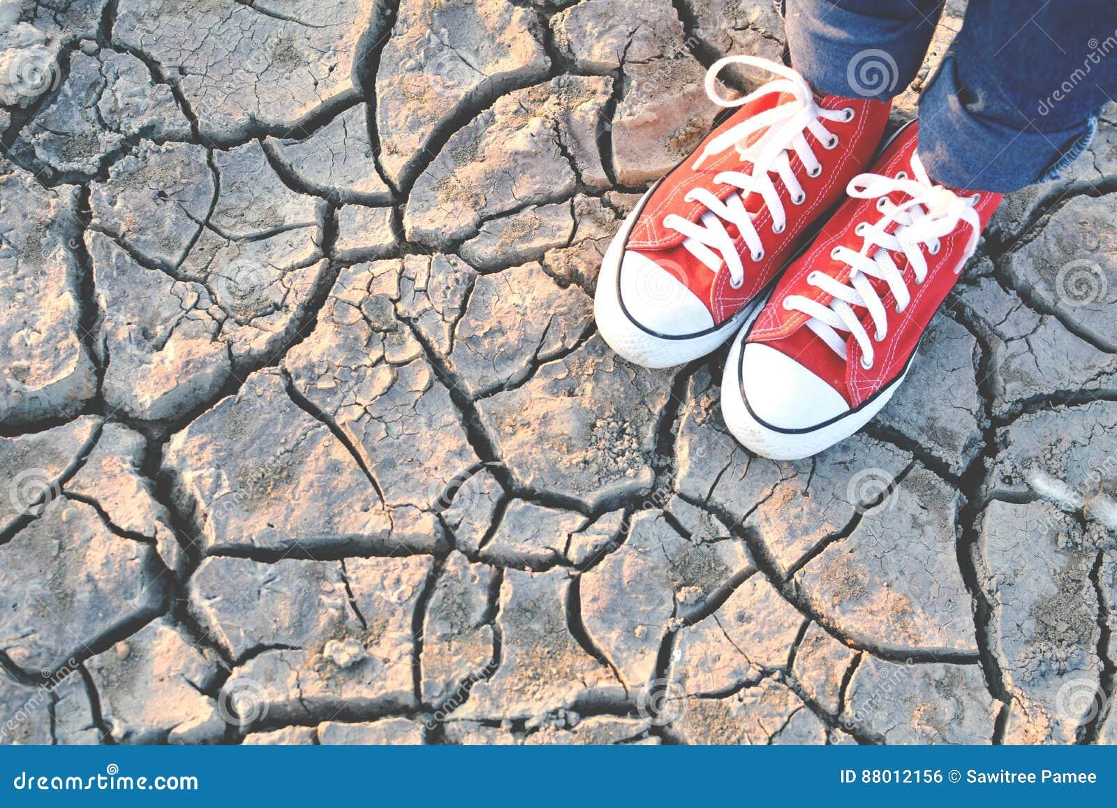 Tennisschoen op barst droge grond