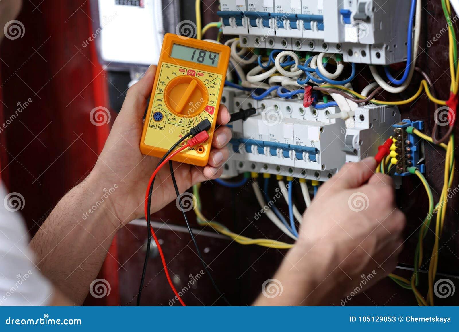 Tensão de medição do eletricista na placa de distribuição
