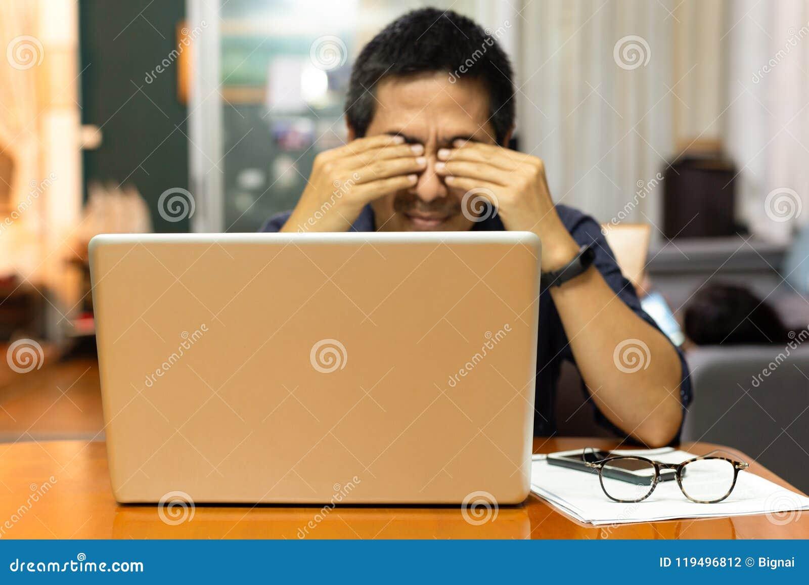 Tensão do sentimento do homem de negócios em seus olhos após ter trabalhado o muito tempo