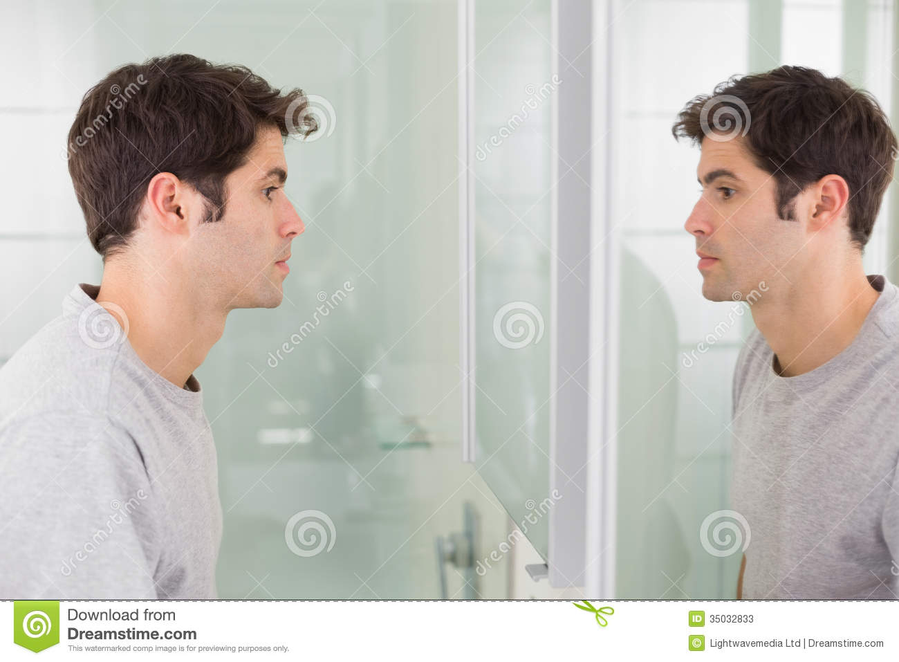 Tensed man looking at self in bathroom mirror stock image for Looking for mirrors