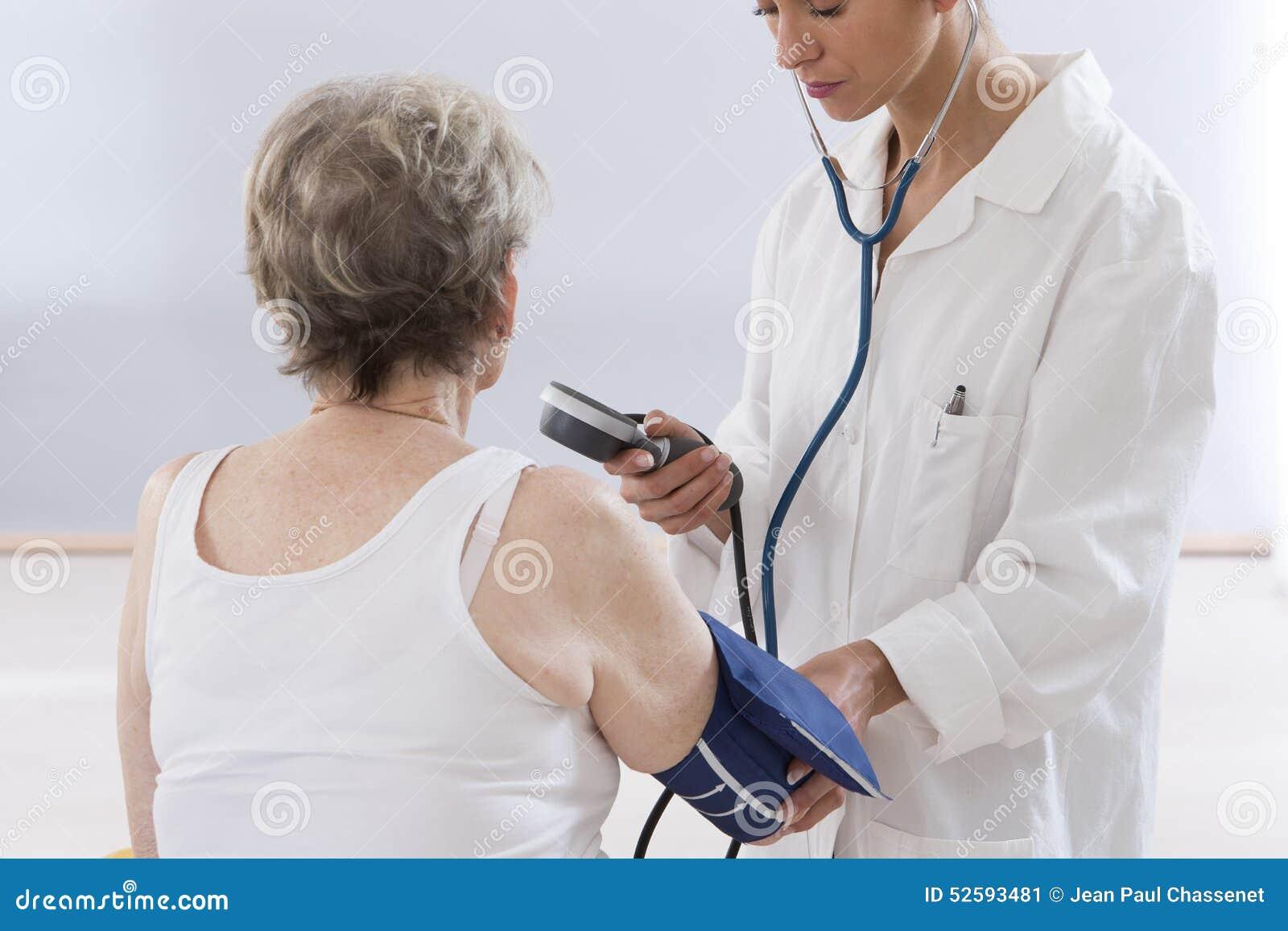 Tension artérielle de mesure de docteur de femme supérieure