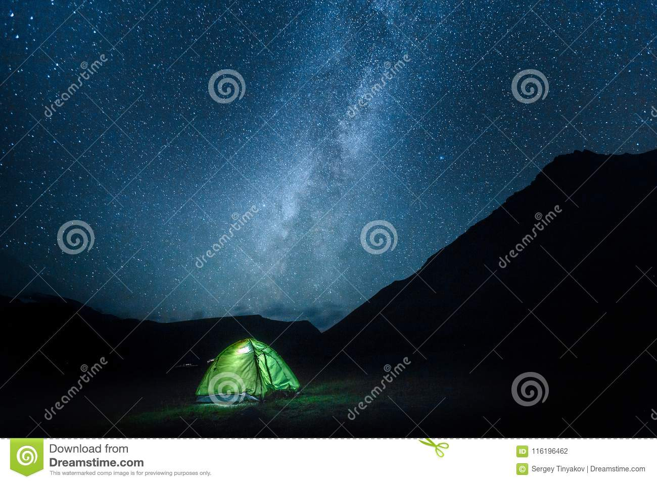 A tent glows under a night sky Milky May full of stars. Elbrus N