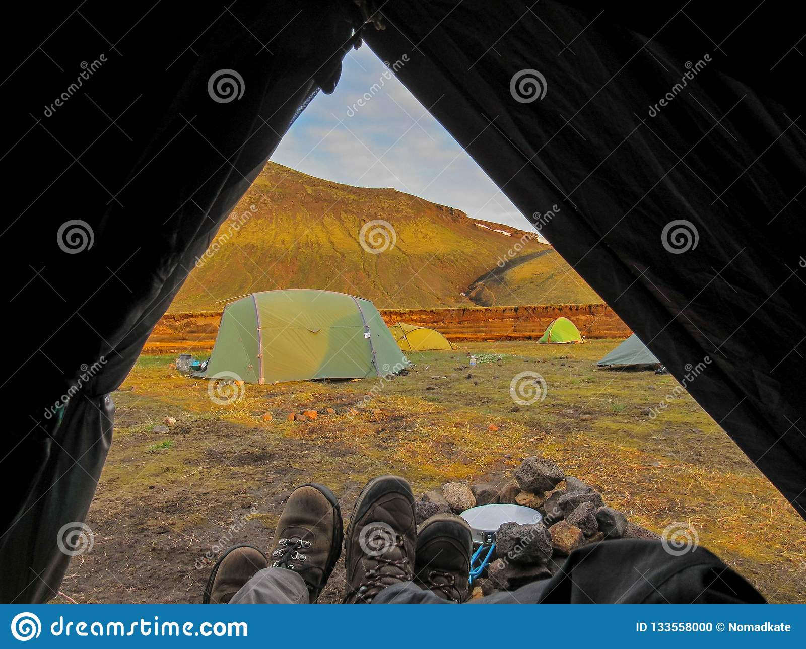 Tent lookout with couple hiking boots and mountain view at sunset, Nature reserve, highlands of iceland