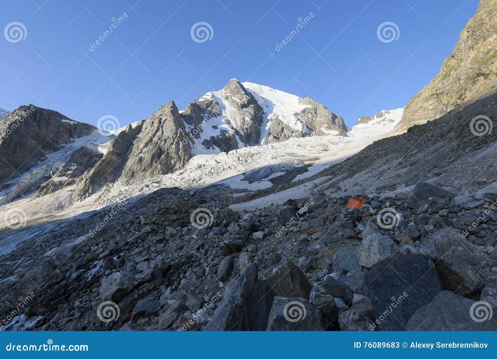 Tente orange parmi des pierres dans le camp des montagnes contre des montagnes et