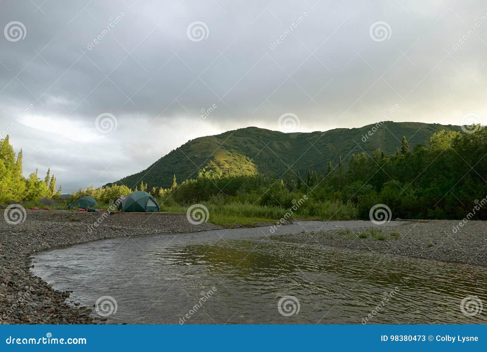 Tenten en kampeerterrein op wilde rivierbank Van Alaska