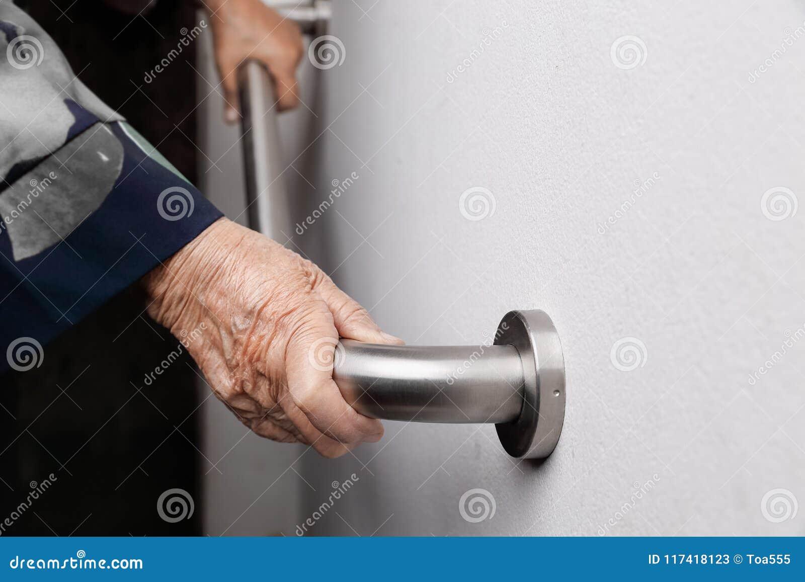 Tenuta anziana della donna sul corrimano per la passeggiata di sicurezza