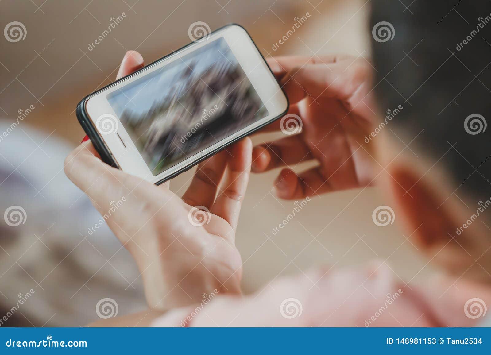 Tenuta del ragazzo del bambino e touch screen asiatici dello smartphone