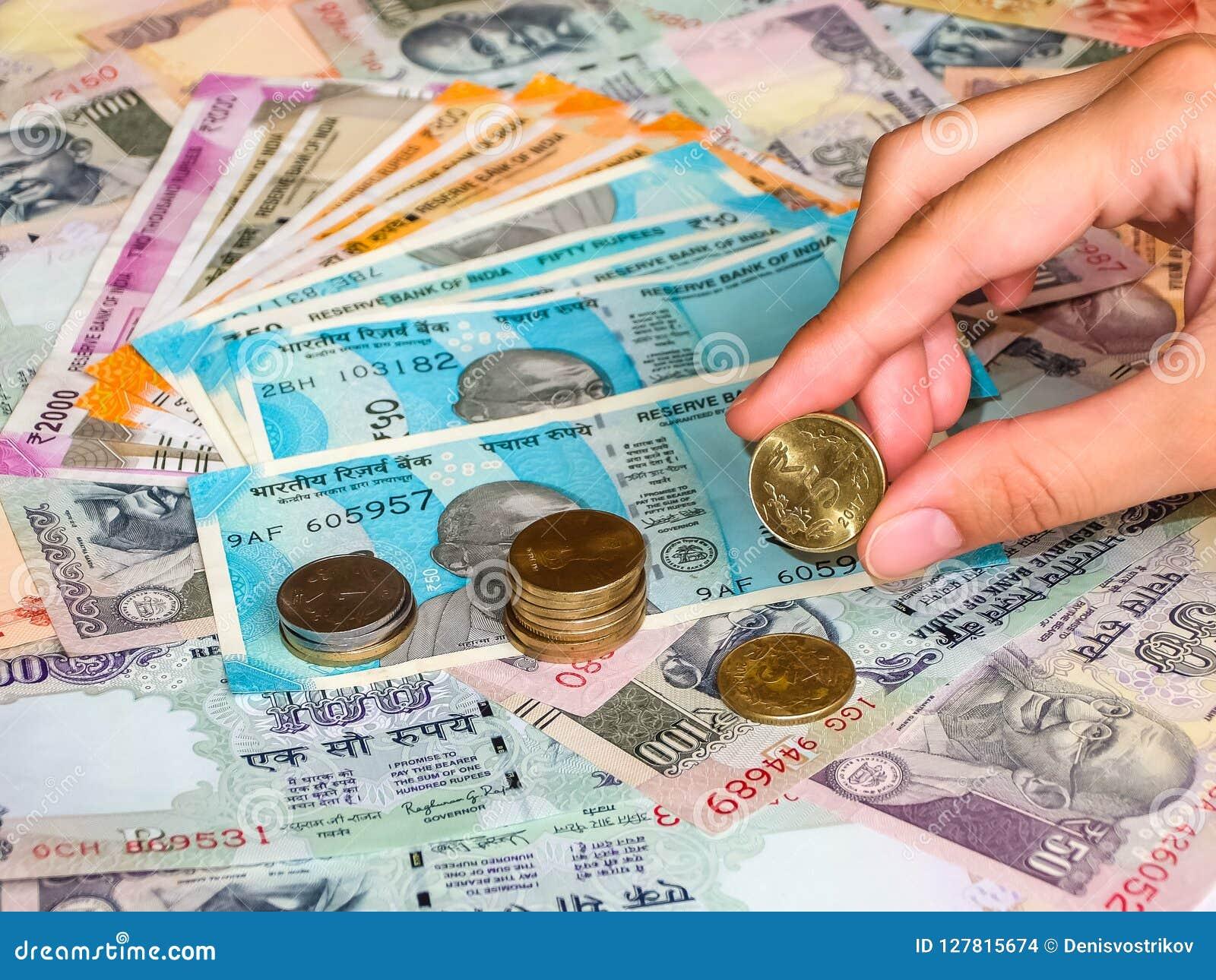 Tenuta della mano una moneta da 5 rupie sopra vecchie e nuove le note indiane delle rupie, primo piano