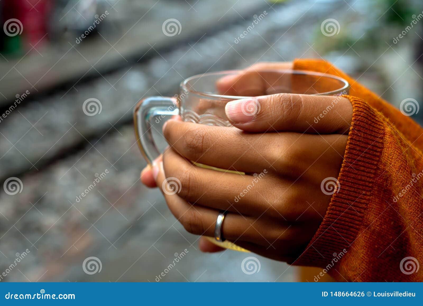 Tenuta della tazza di t? dal pullover delle rotaie che riguarda le mani da un terzo