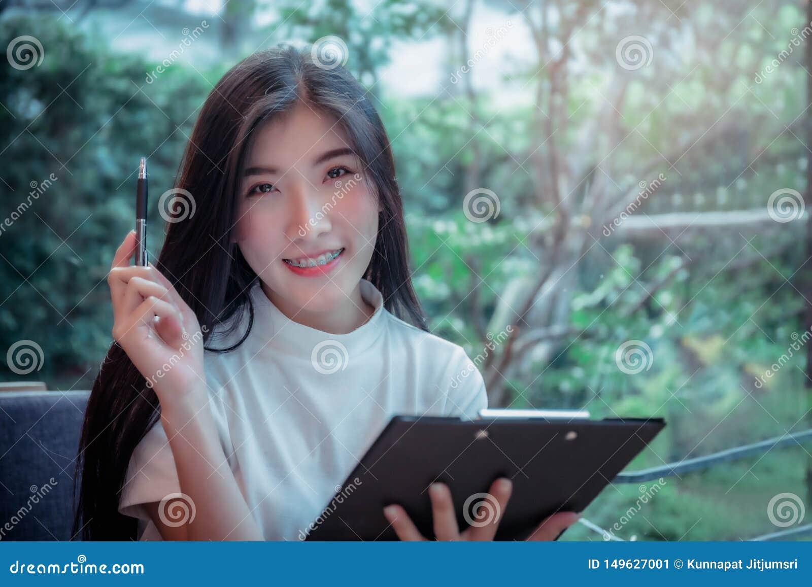 Tenuta di stile di affari della ragazza asiatica una penna e una cosa positiva sorridente di emozione del giorno