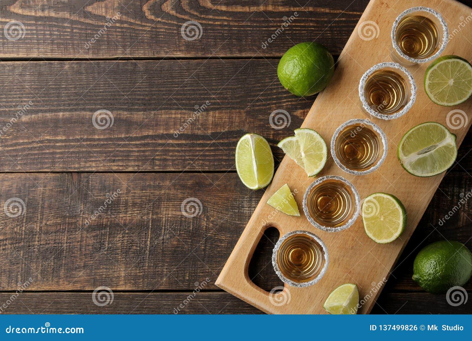 Tequila dell oro in un vetro sparato di vetro con sale e calce su un fondo di legno marrone Vista superiore con spazio per testo