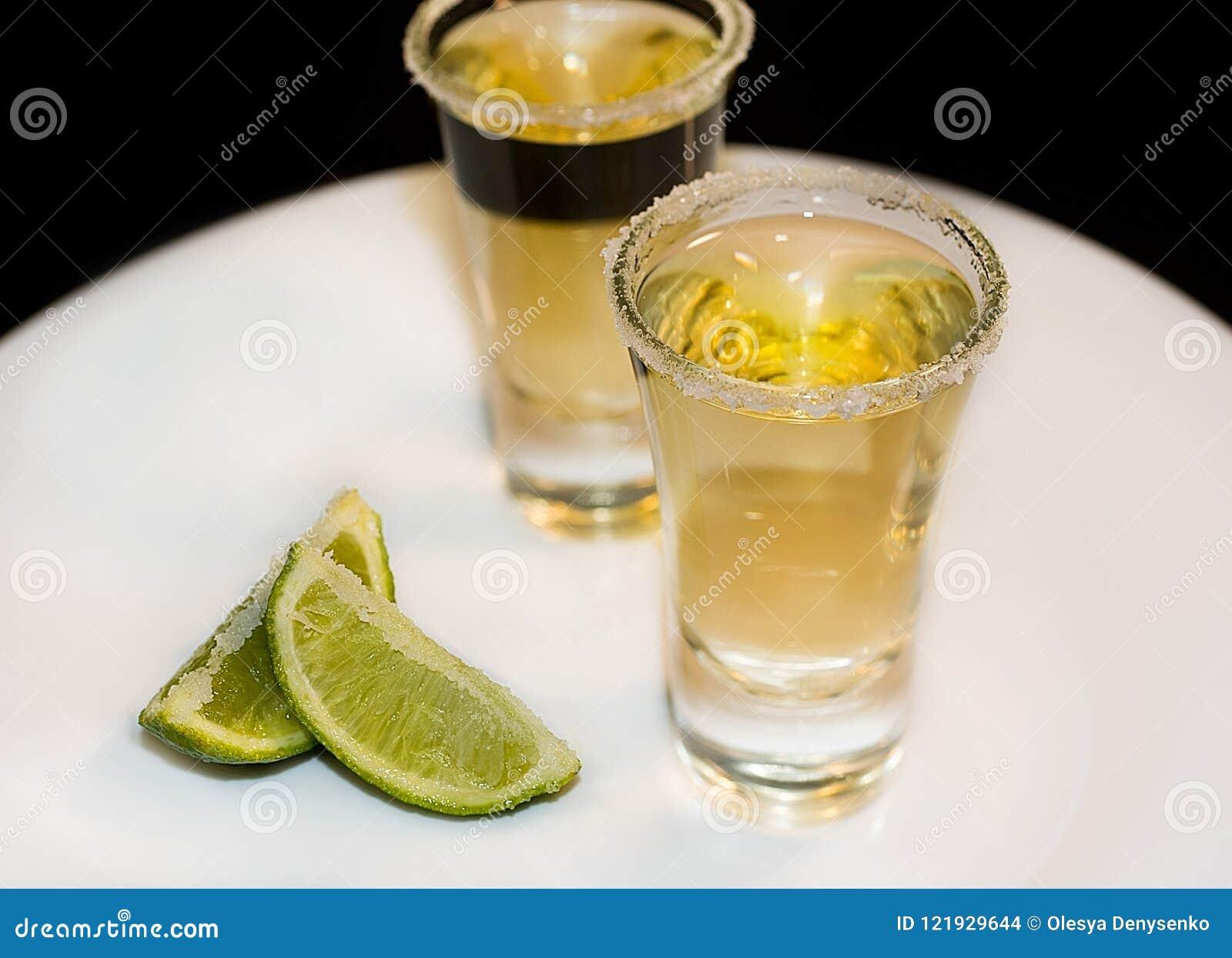 Tequila i små exponeringsglas med limefrukt