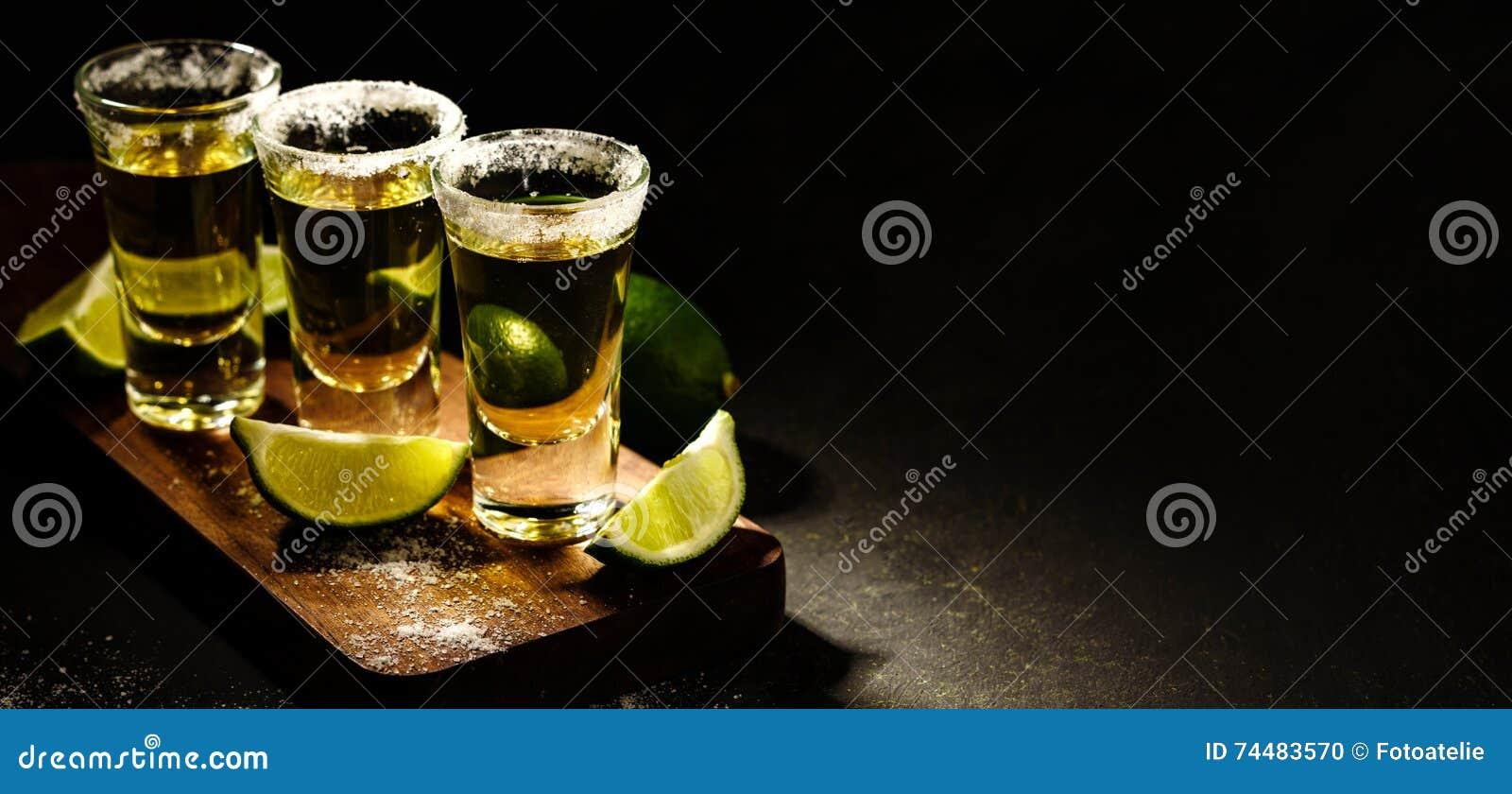 Tequila messicana dell oro con calce e sale sulla tavola di legno