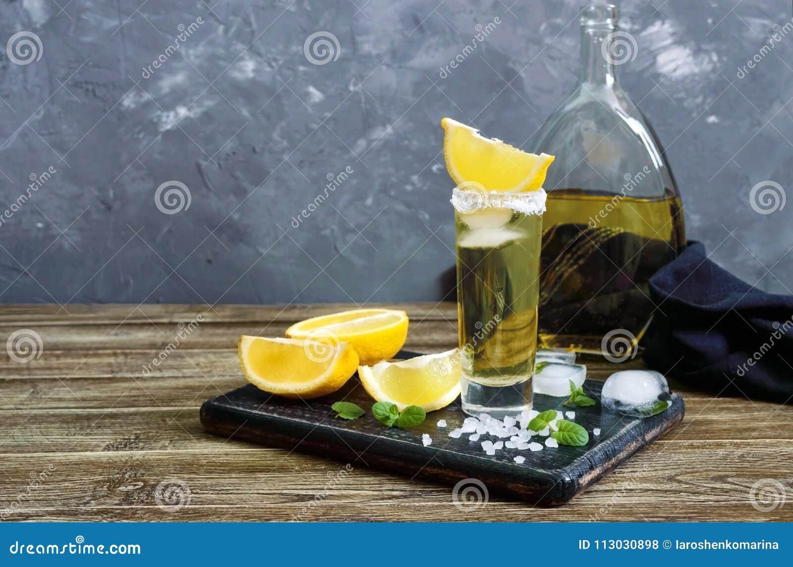 Tequila mexicano del oro en el vaso de medida con el limón y la sal del mar en la tabla oscura