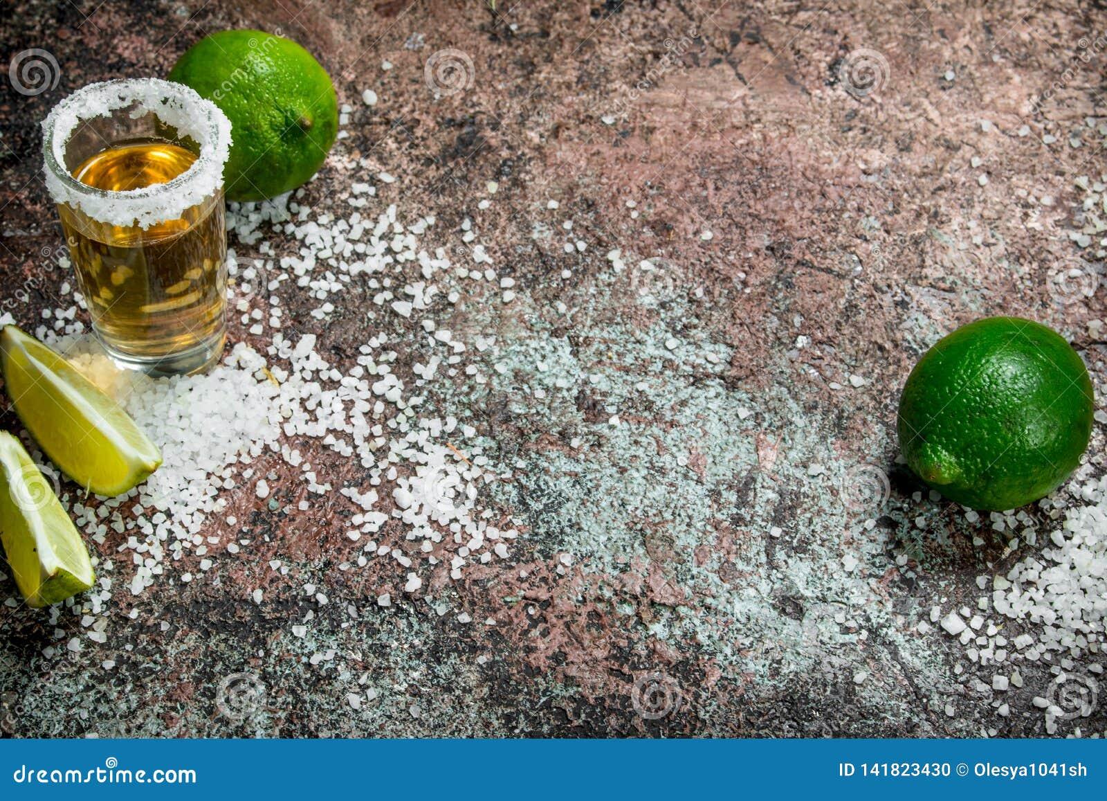 Tequilaen i ett skjutit exponeringsglas med saltar och skivor av ny limefrukt