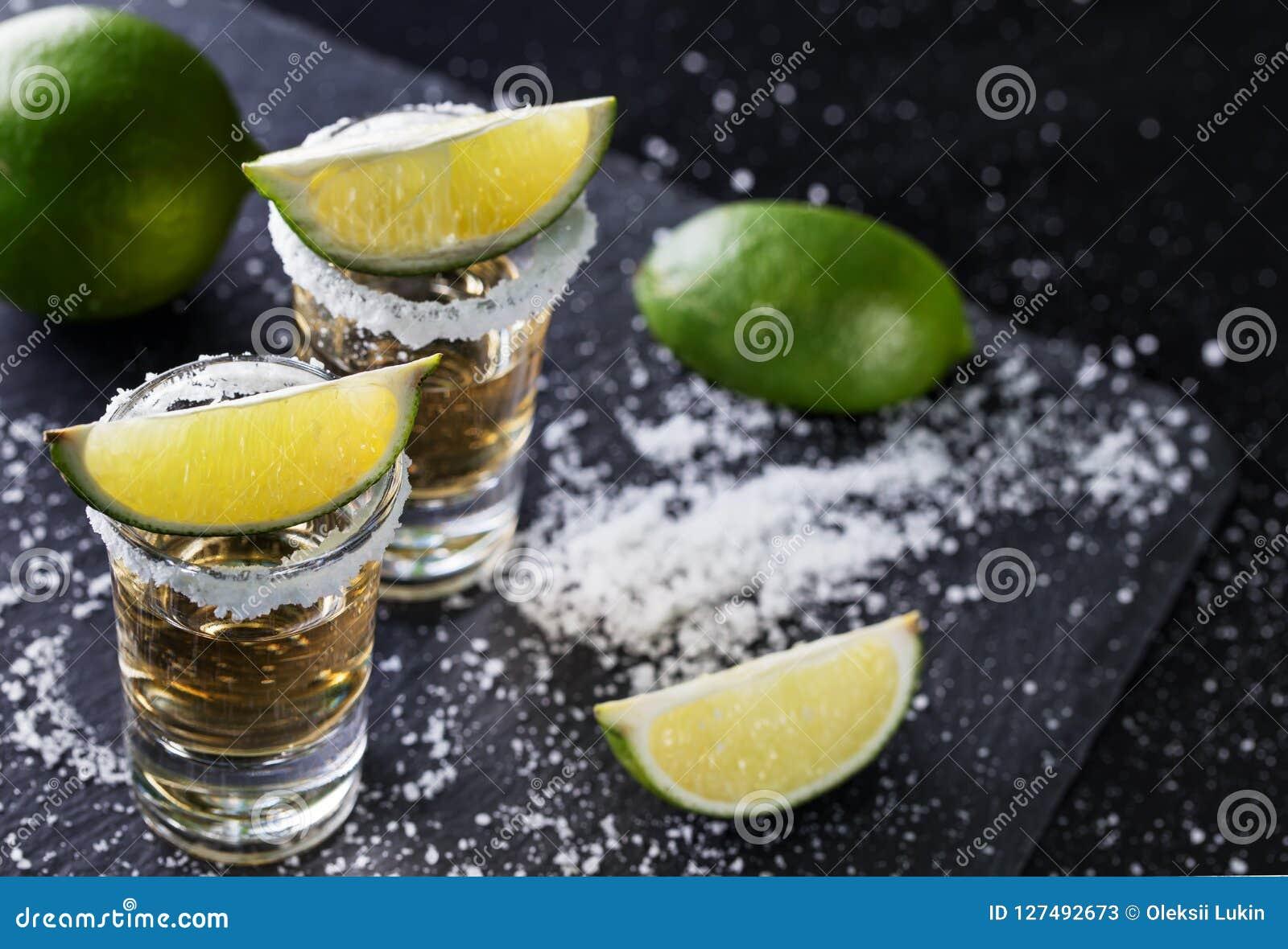 Tequilaen med skivad och hel limefrukt och saltar