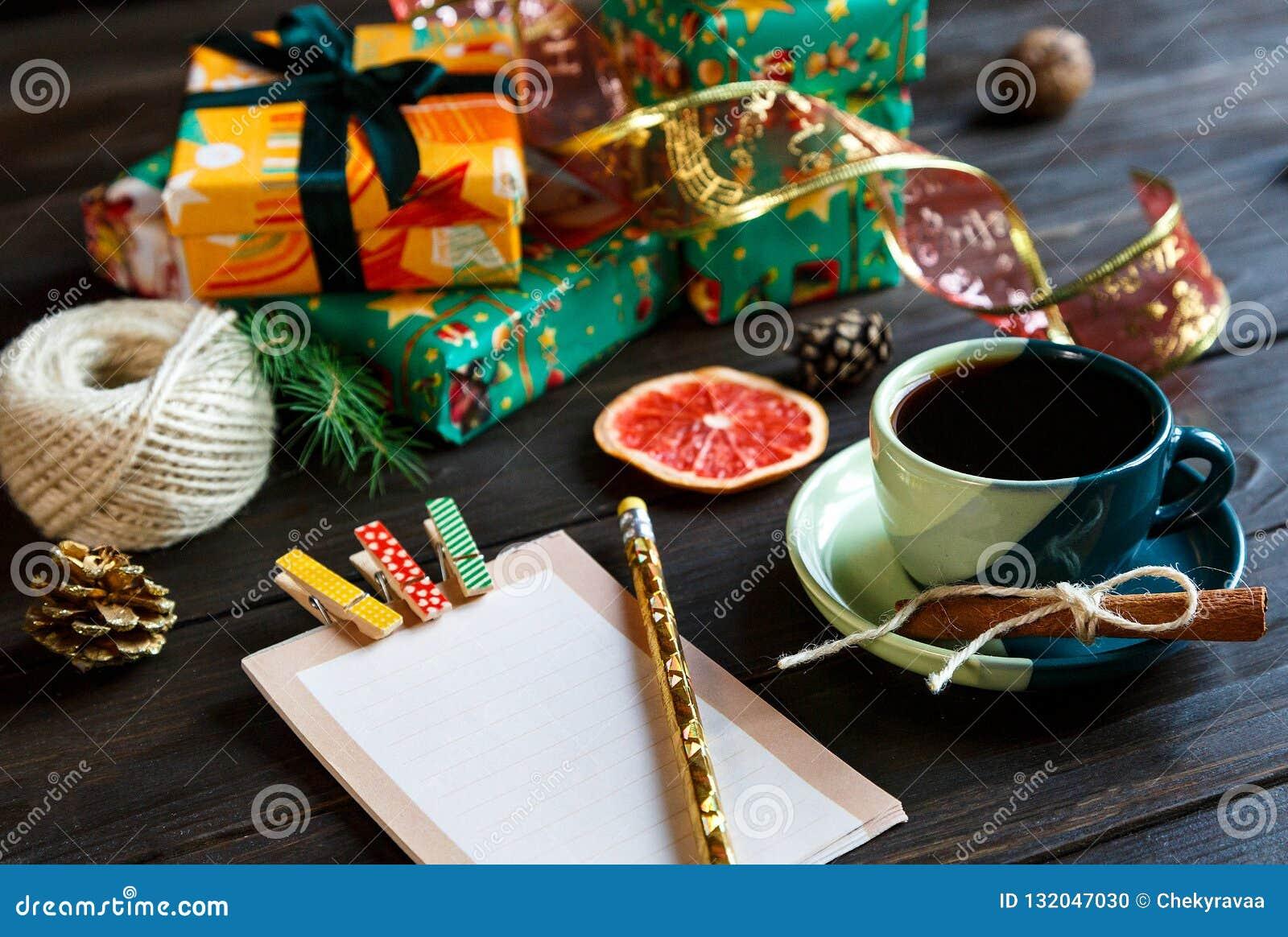 Teraźniejszość dla przyjaciół i rodziny w papierze pomarańczowym i zielonym, notepad, filiżanka kawy na drewnianym tle na zakupy