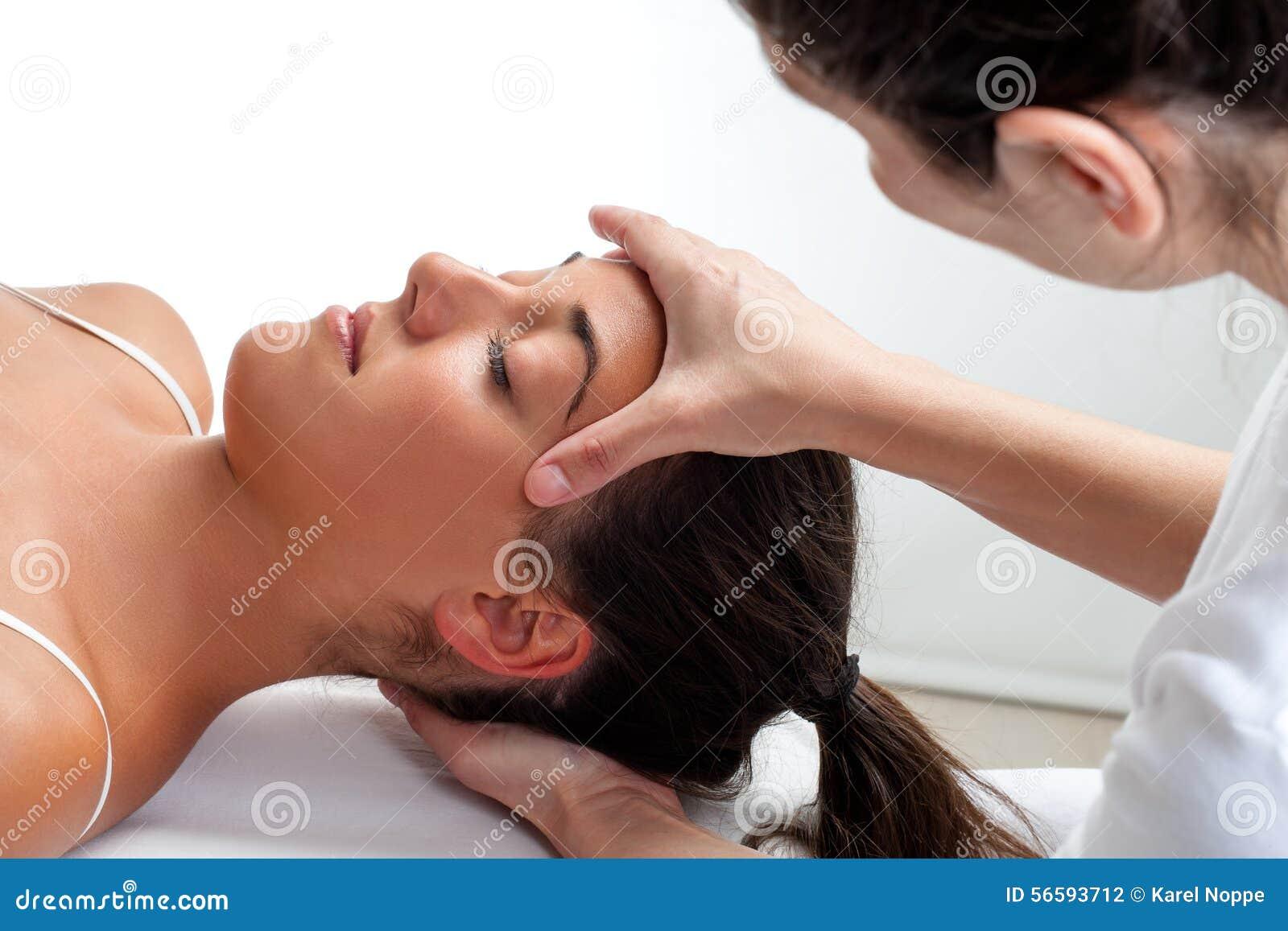 Terapeut som gör läka behandling på kvinnas huvud