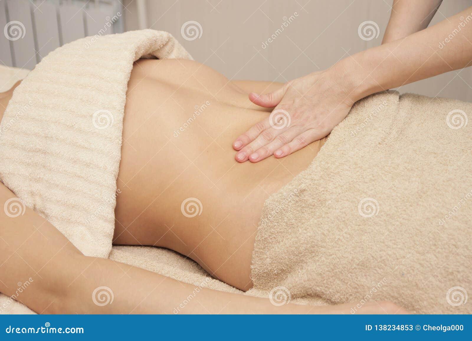 Terapeuta del masaje que hace un masaje térmico para el abdomen para una mujer