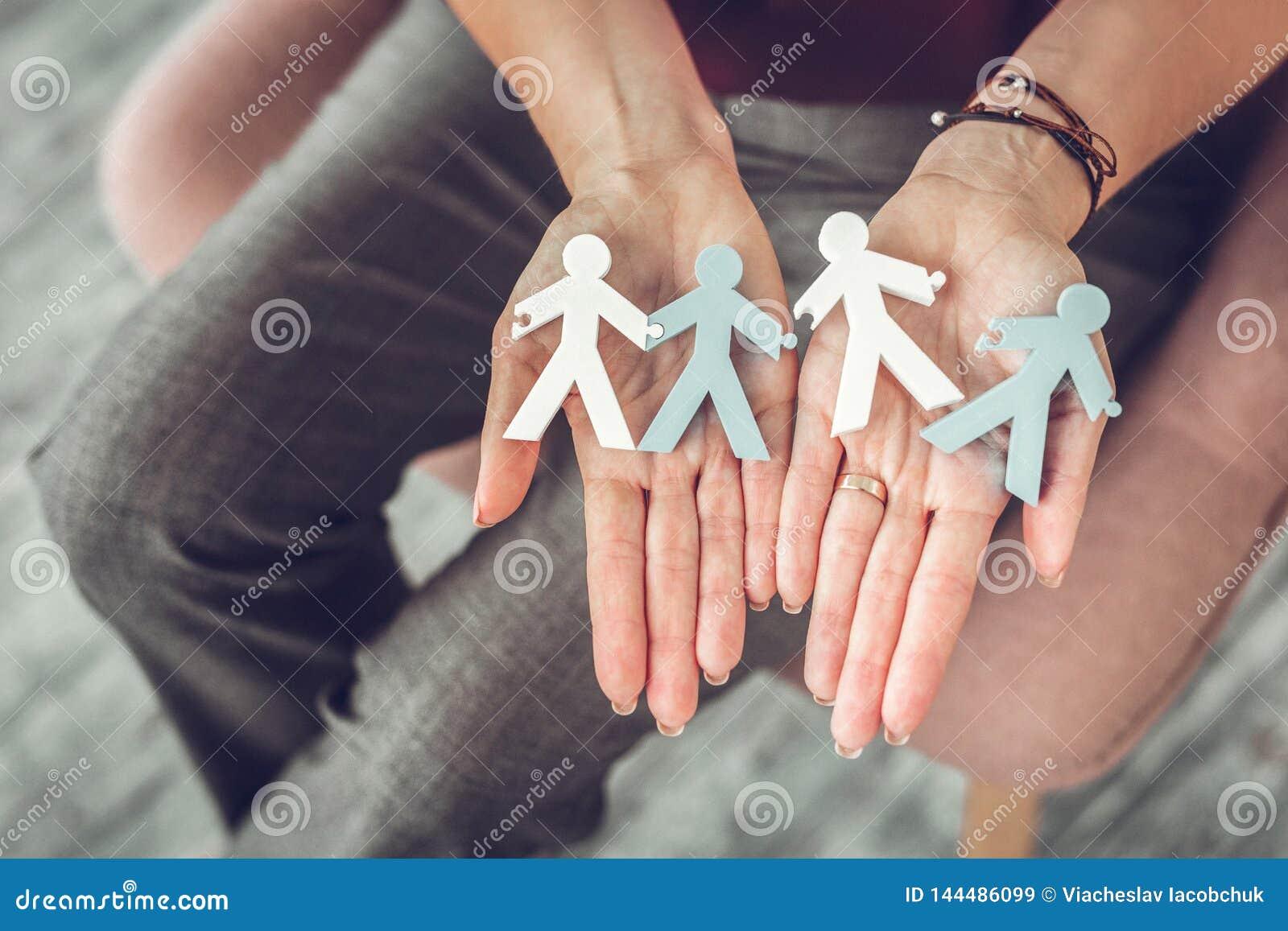 Terapeuta fêmea da família que guarda modelos pequenos dos pares nas mãos