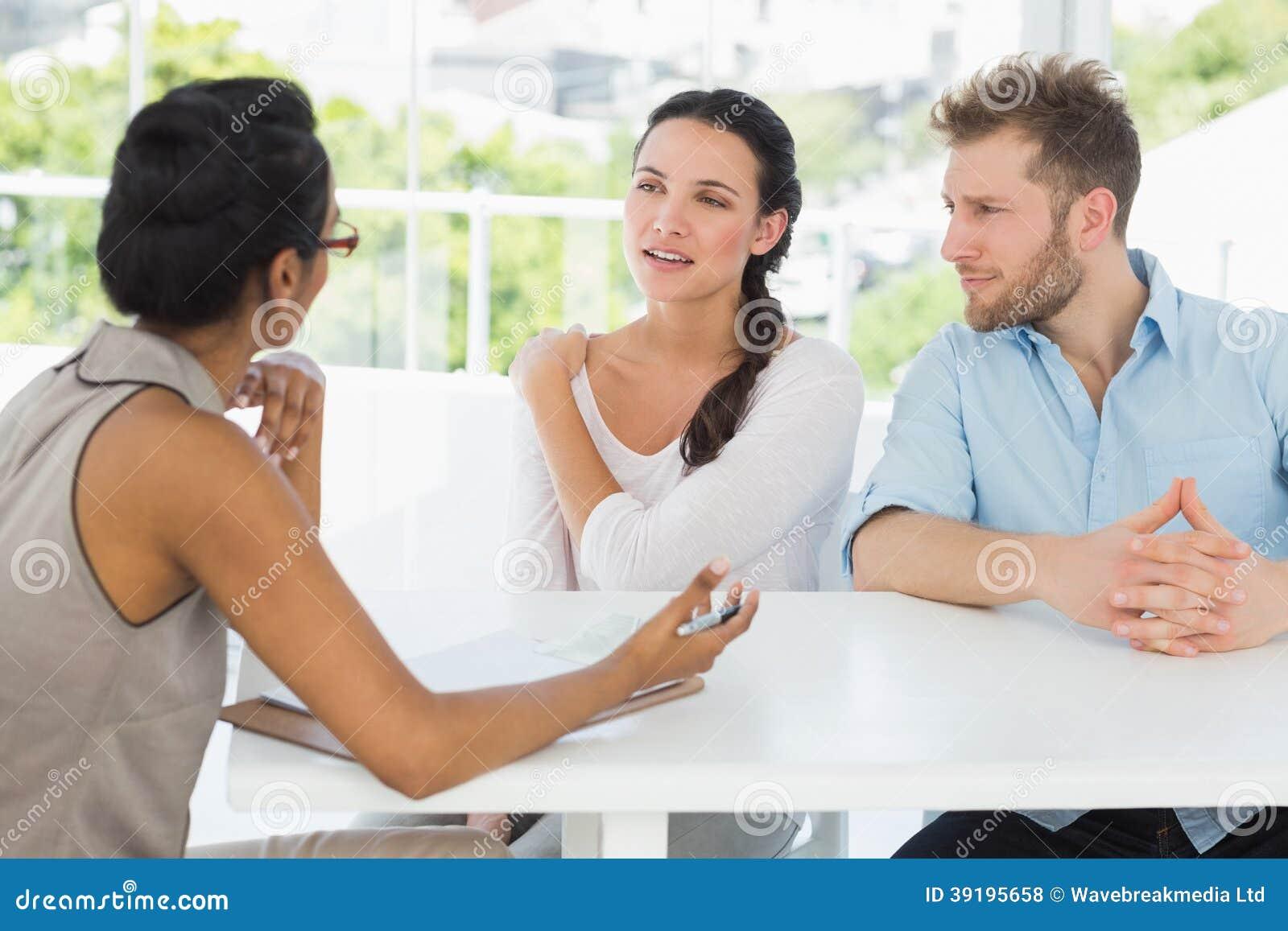 Terapeuta que habla con los pares que se sientan en el escritorio