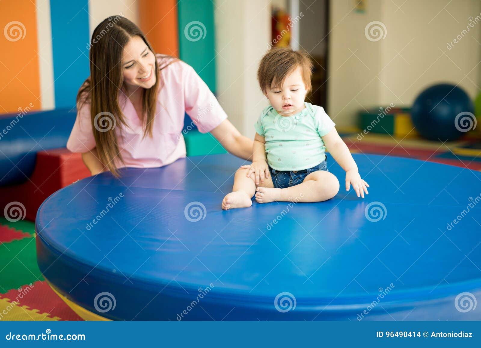 Terapista che aiuta un bambino a praticare equilibrio