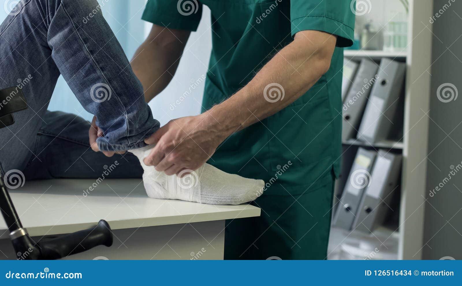Terapista fisico che mette gesso fuso sulla gamba rotta dei pazienti, trattamento di trauma