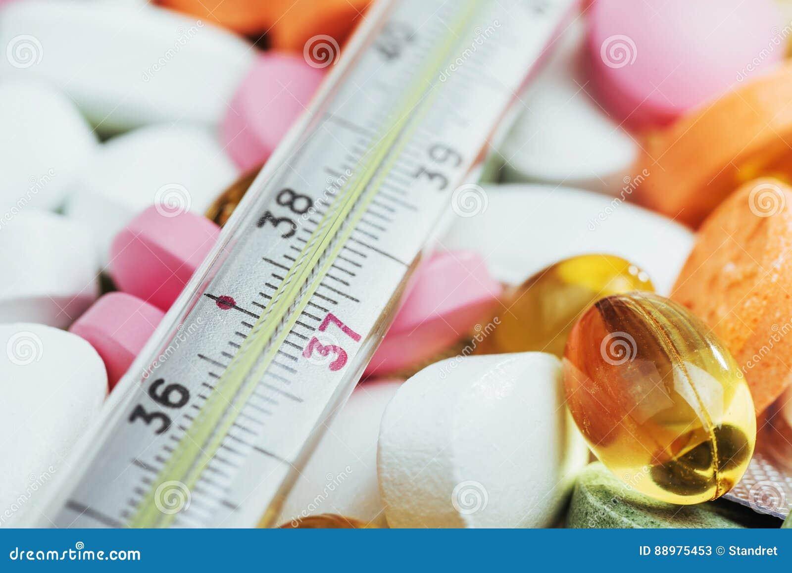 Termômetro e tipos coloridos diferentes de comprimidos Conceito médico da saúde ou das drogas