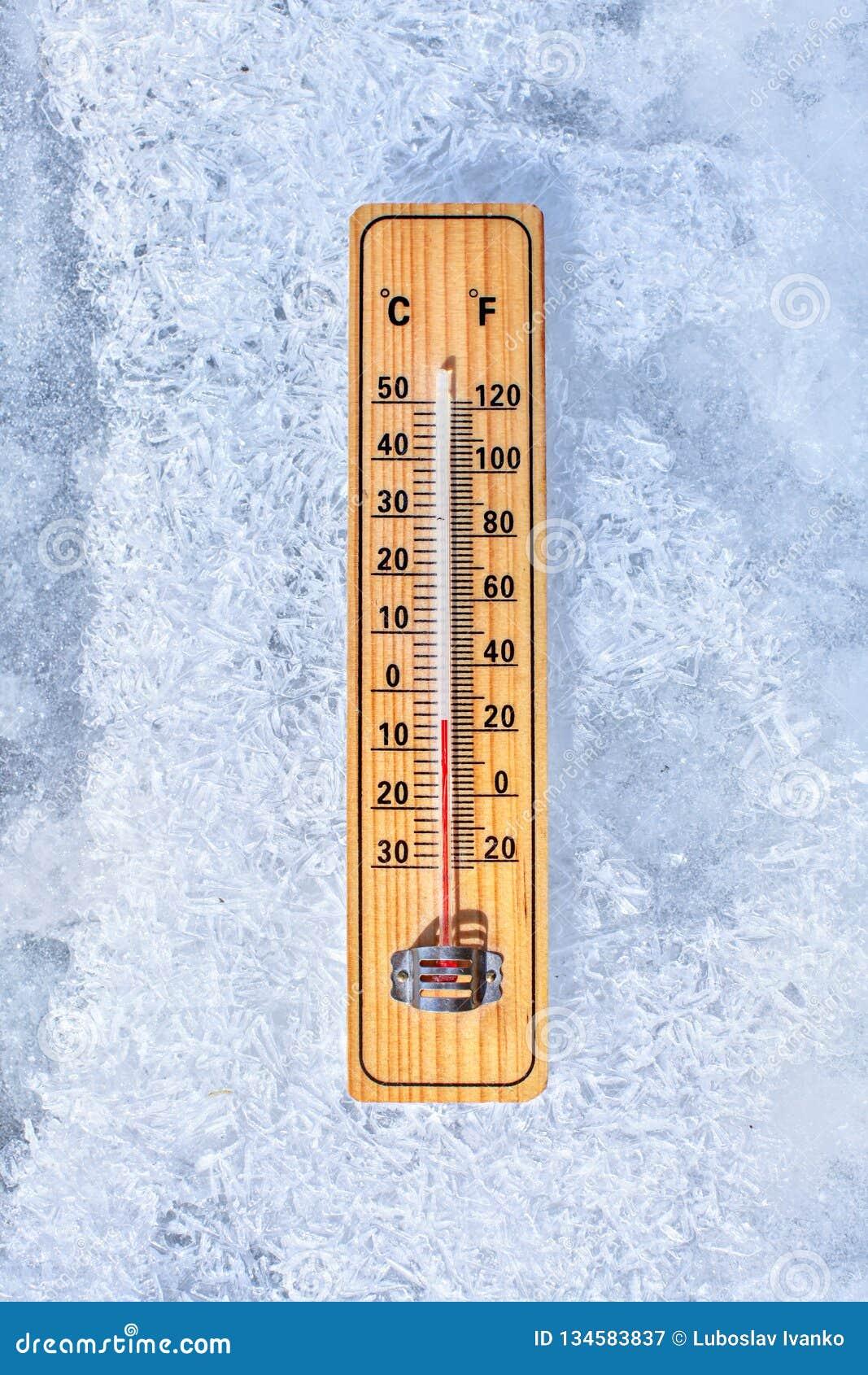 Termômetro que coloca no gelo, mostrando menos 5 graus Sun que brilha do lado inverno/baixas temperaturas que vêm, conceito