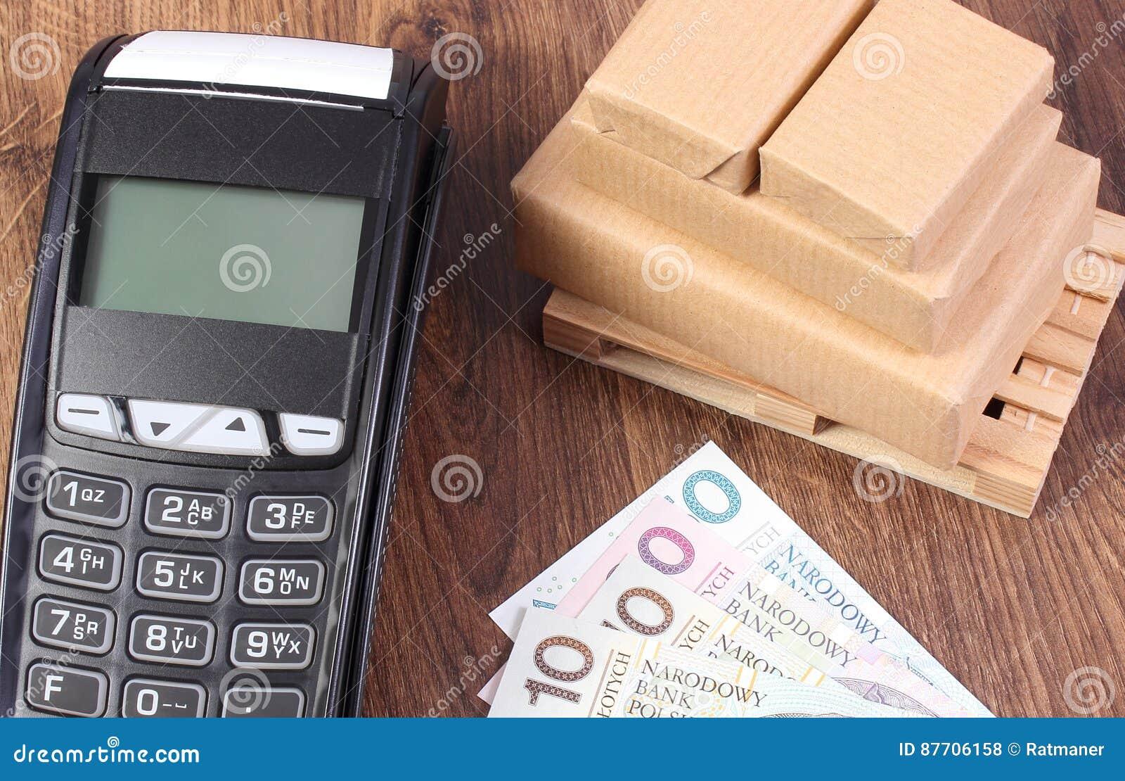 Terminal de paiement, argent polonais de devise et boîtes enveloppées sur la palette en bois