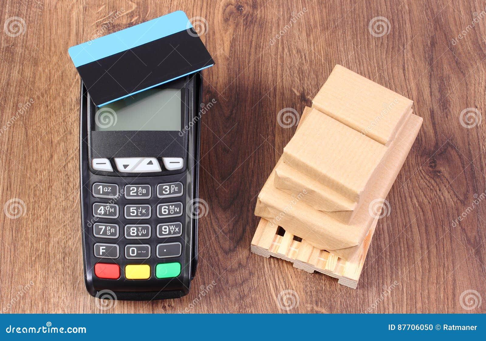Terminal de paiement avec la carte de crédit et boîtes enveloppées sur la palette en bois, payant des produits et l expédition