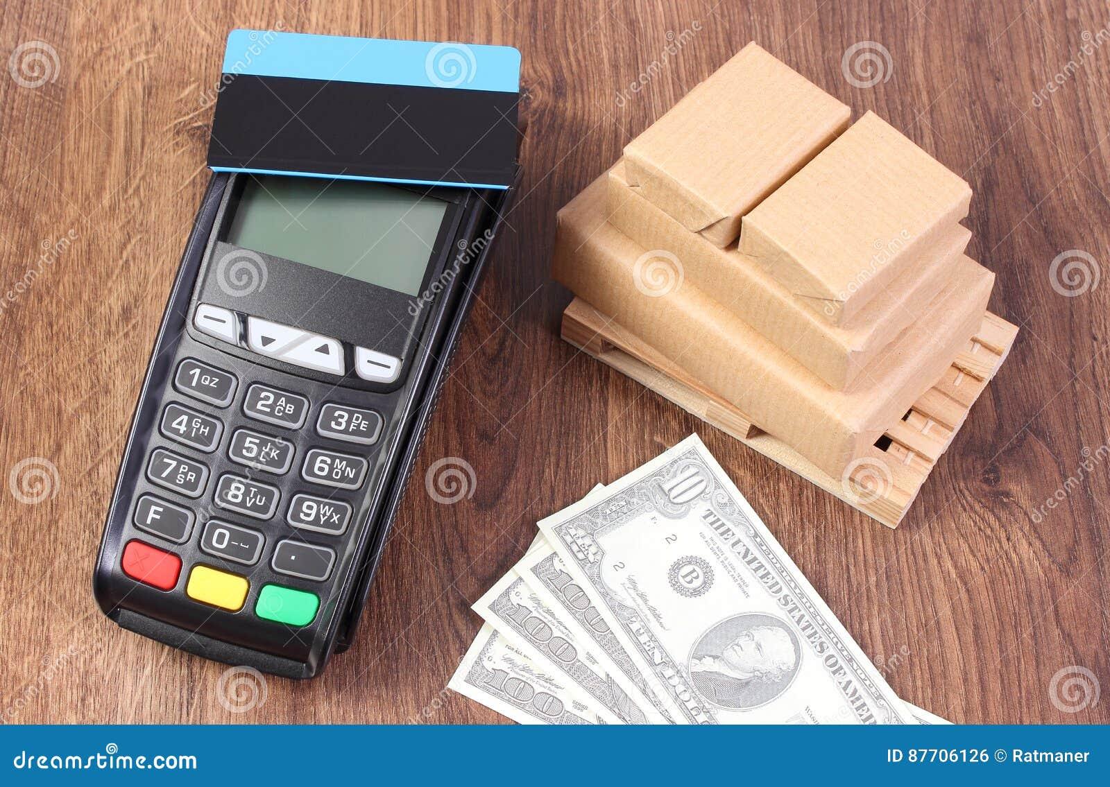 Terminal de paiement avec la carte de crédit, le dollar de devises et les boîtes enveloppées sur la palette en bois