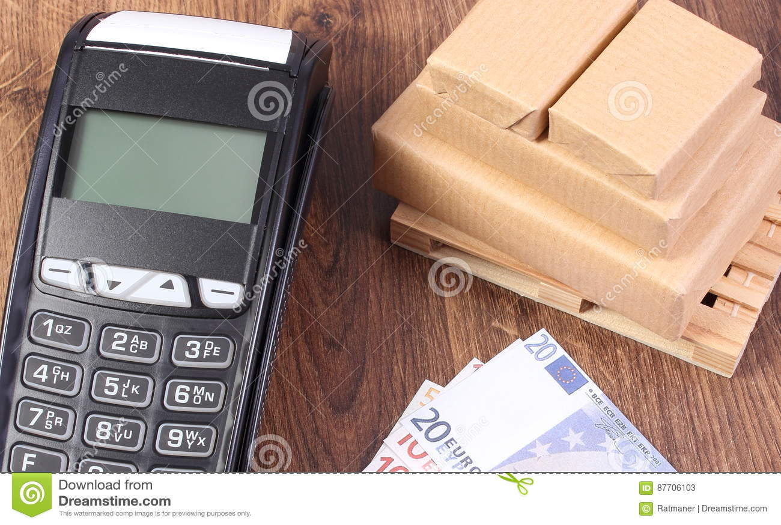 Terminal de paiement, euro de devises et boîtes enveloppées sur la palette en bois