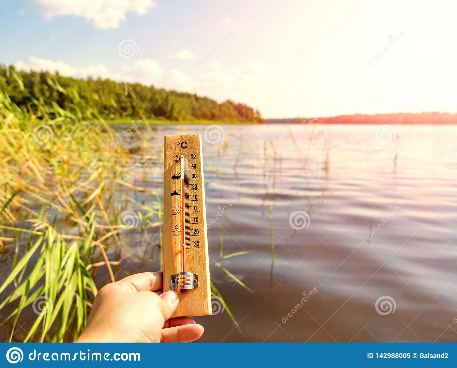 Termometervisning som 30 grader är celsius av värme mot bakgrunden av sjövattnet och den blåa himlen i solljus
