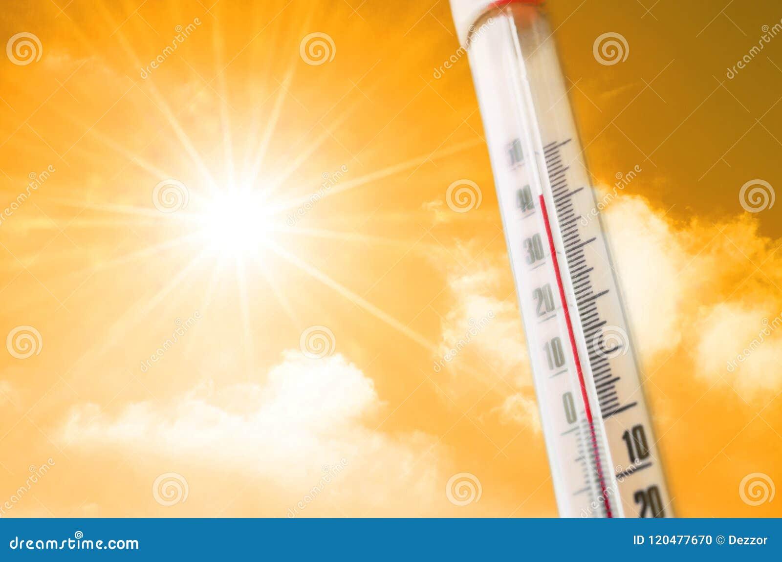 Termometro contro lo sfondo di un incandescenza calda di giallo arancio delle nuvole e del sole, concetto di caldo