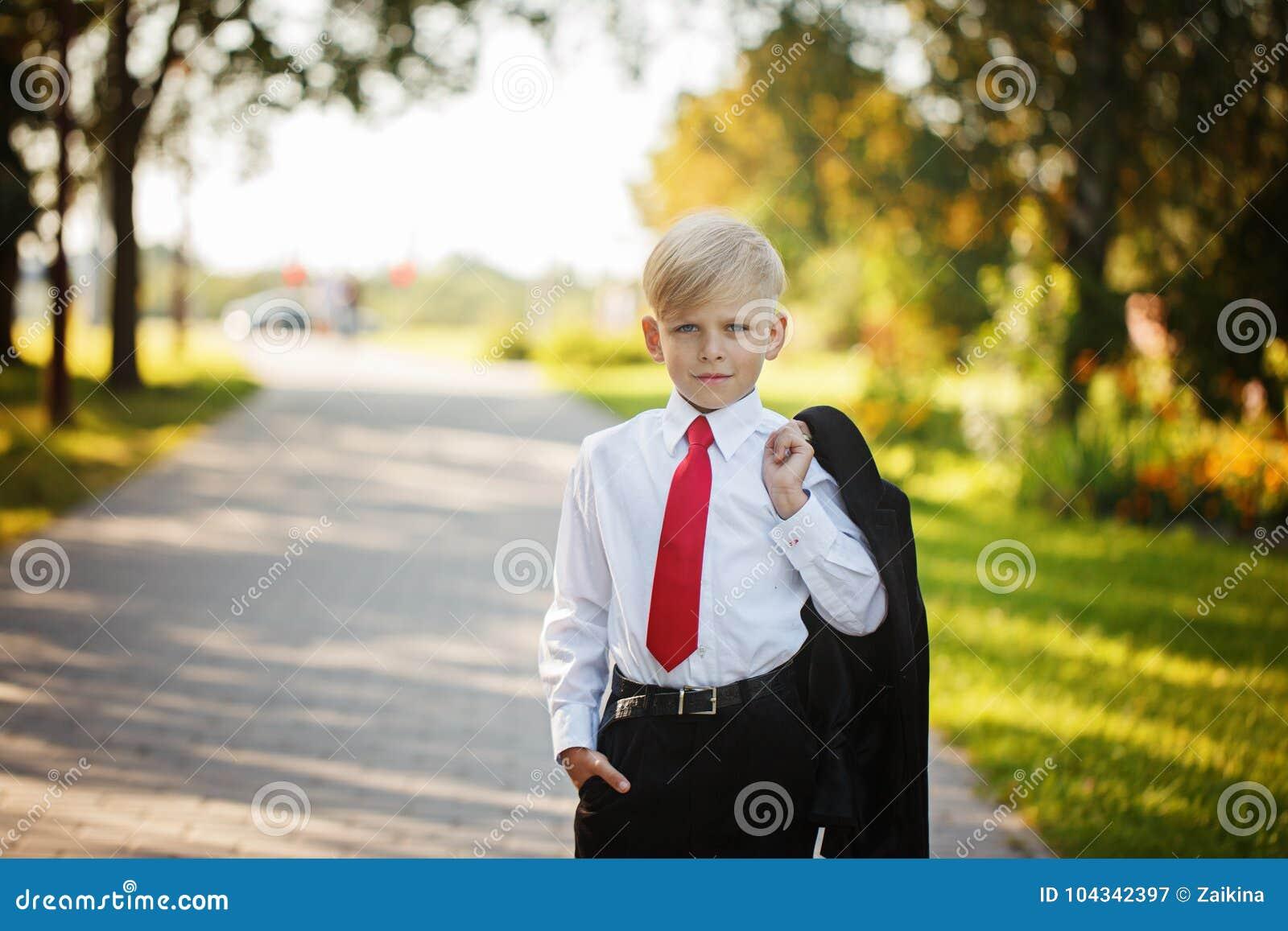 Terno de negócio vestindo do rapaz pequeno e laço vermelho no fundo da natureza