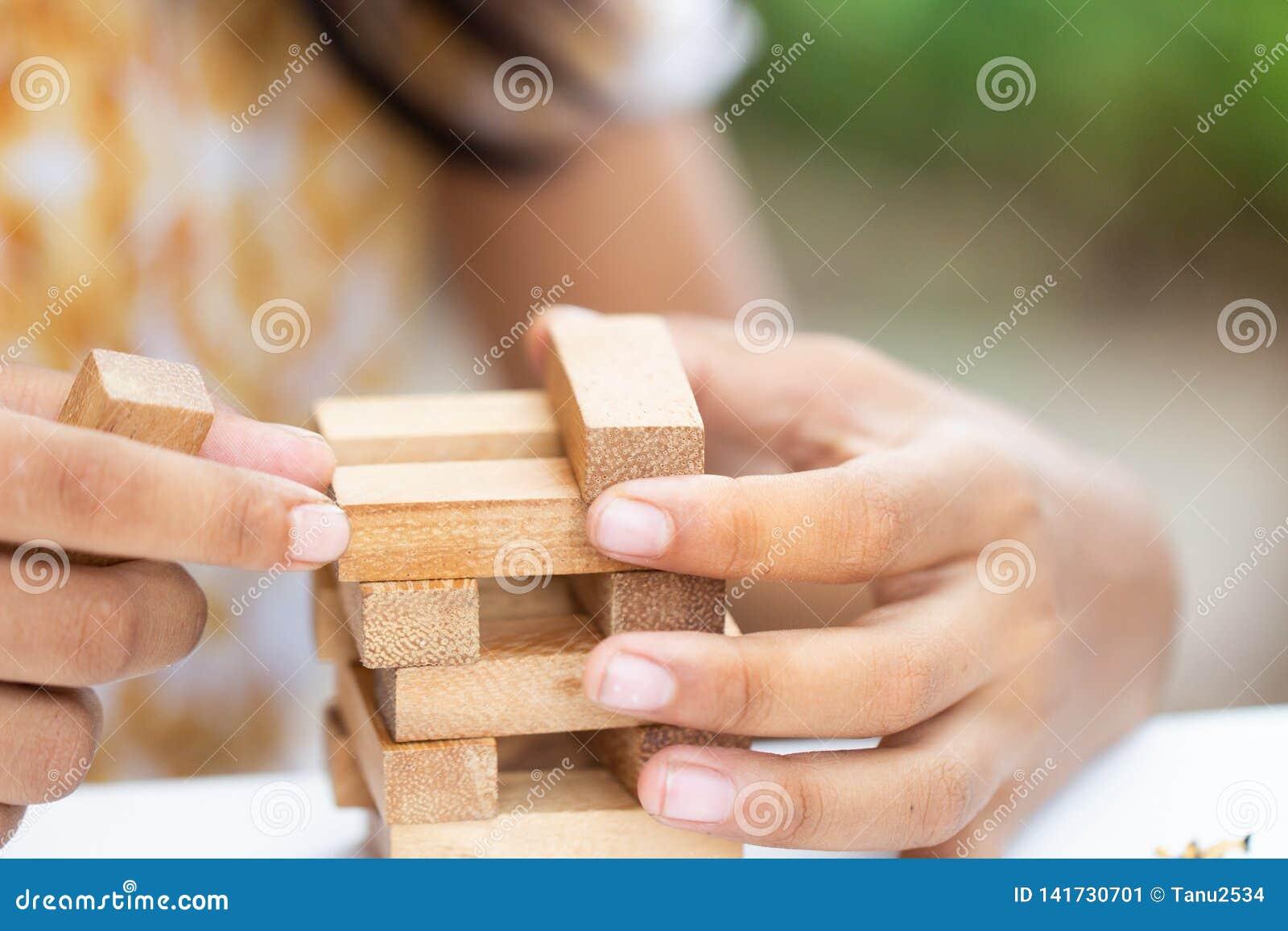Terra arrendada da mão da menina que joga o bloco de madeira,