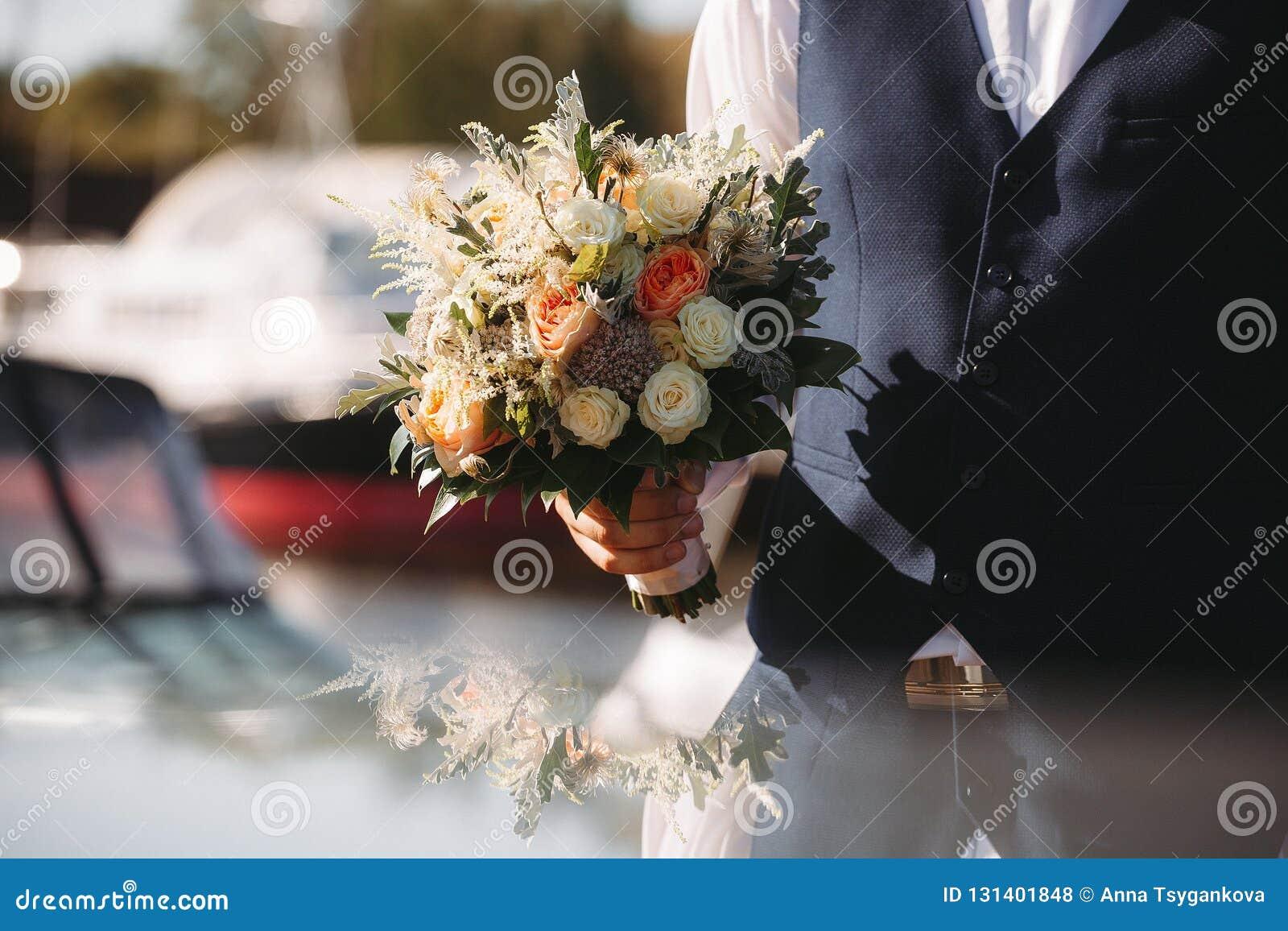 Terra arrendada nas mãos delicadas, ramalhete nupcial caro, na moda do noivo do casamento das flores