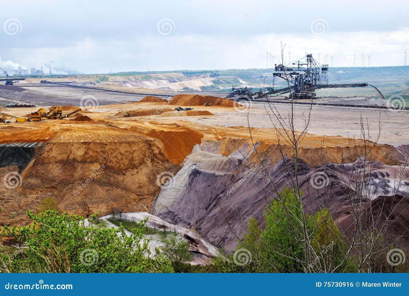 A terra destruída mergulha durante o poço aberto do lignite (carvão marrom) mini