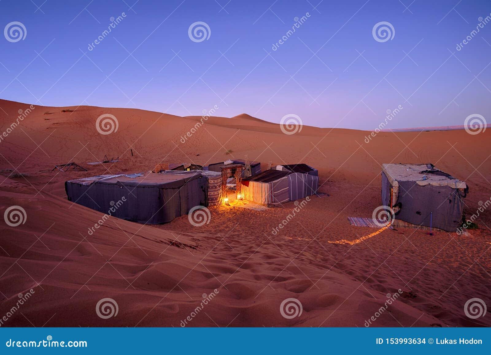 Terrain de camping touristique de désert avec des tentes derrière les dunes de sable