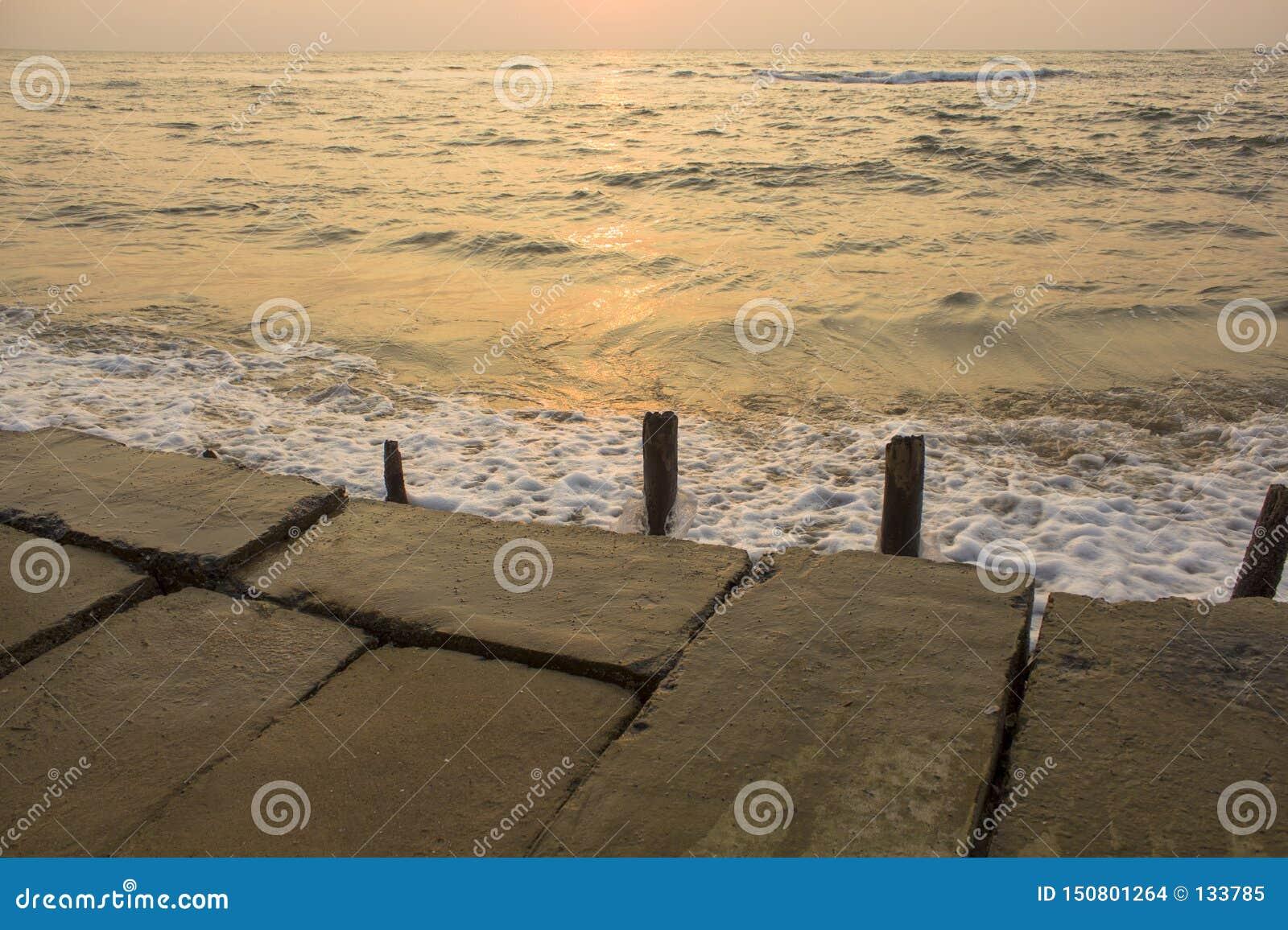 Terraplenagem concreta velha com colagem de cercas de madeira destruídas contra o contexto de ondas do mar durante o por do sol