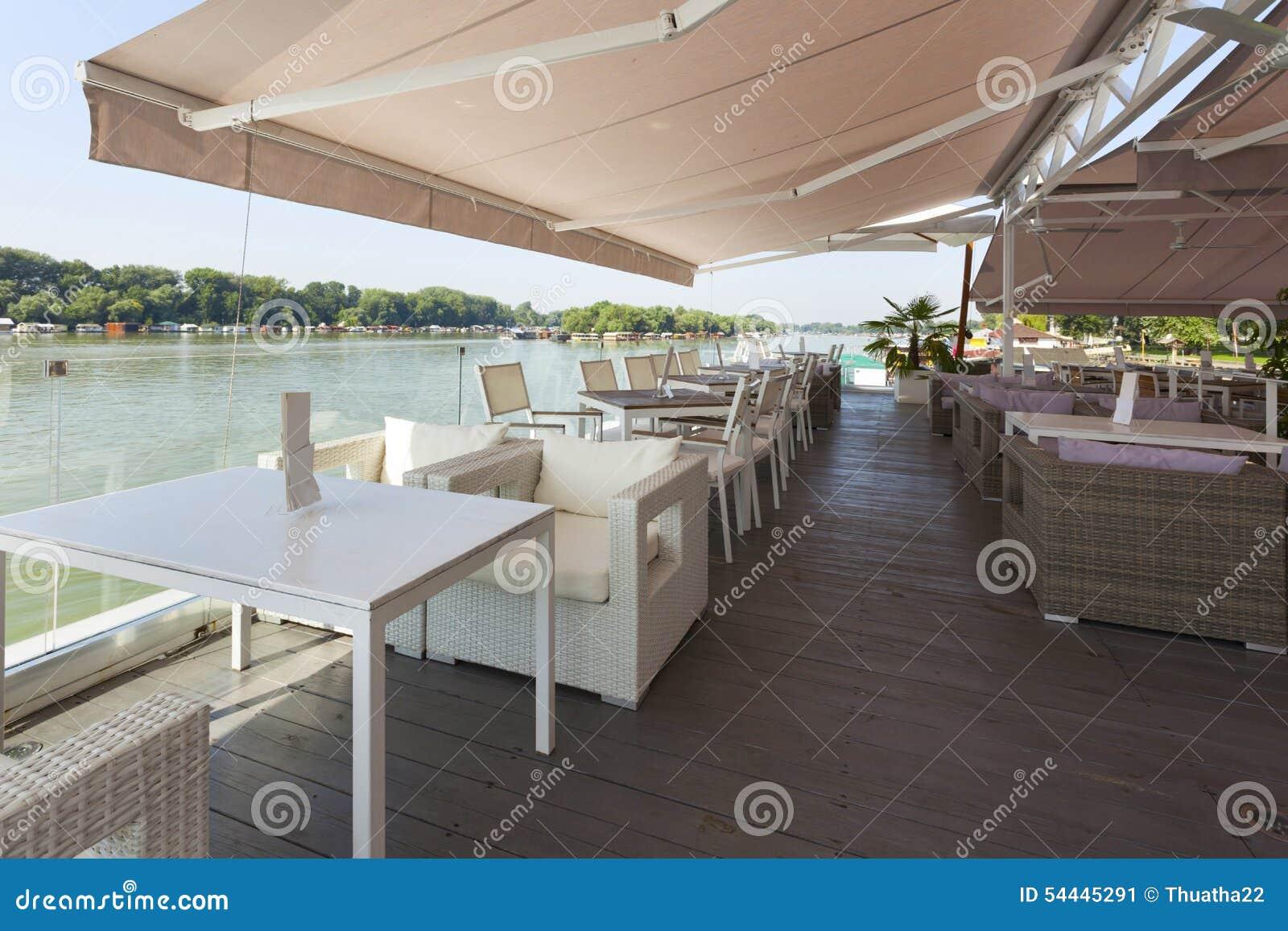 Terrasse moderne de café de rive pendant le matin