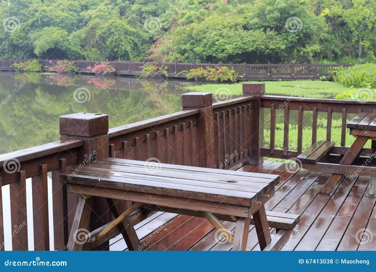 terraza de madera de la orilla del lago en lluvia foto de archivo