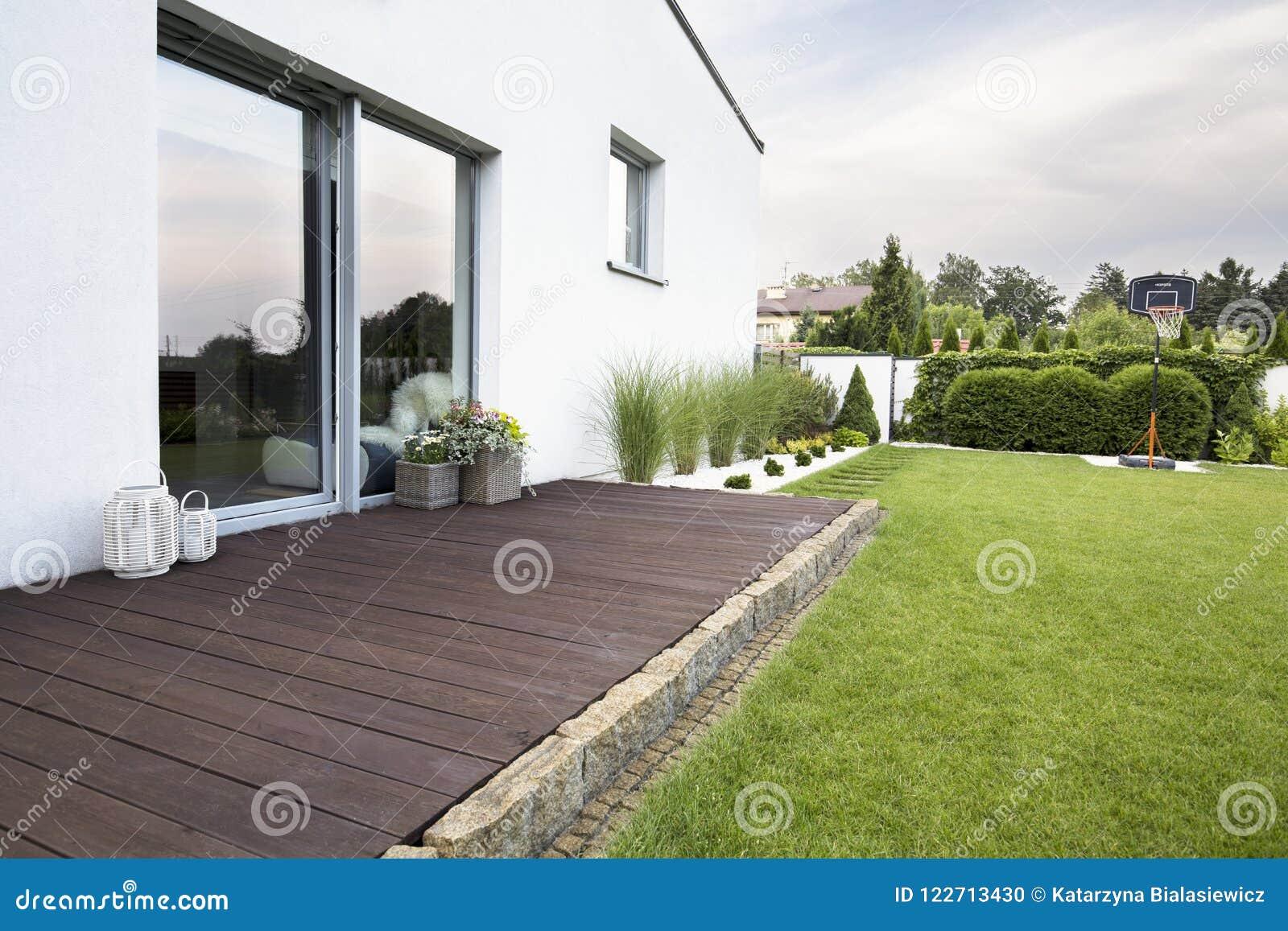 Terrazzo vuoto di legno della casa bianca con erba verde e gli