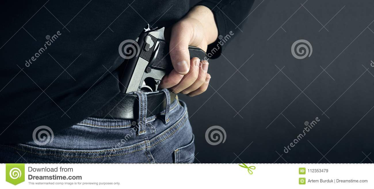 Terrorist thief man holding gun in his hand. Hidden gun. Isolated on dark background. copy space.