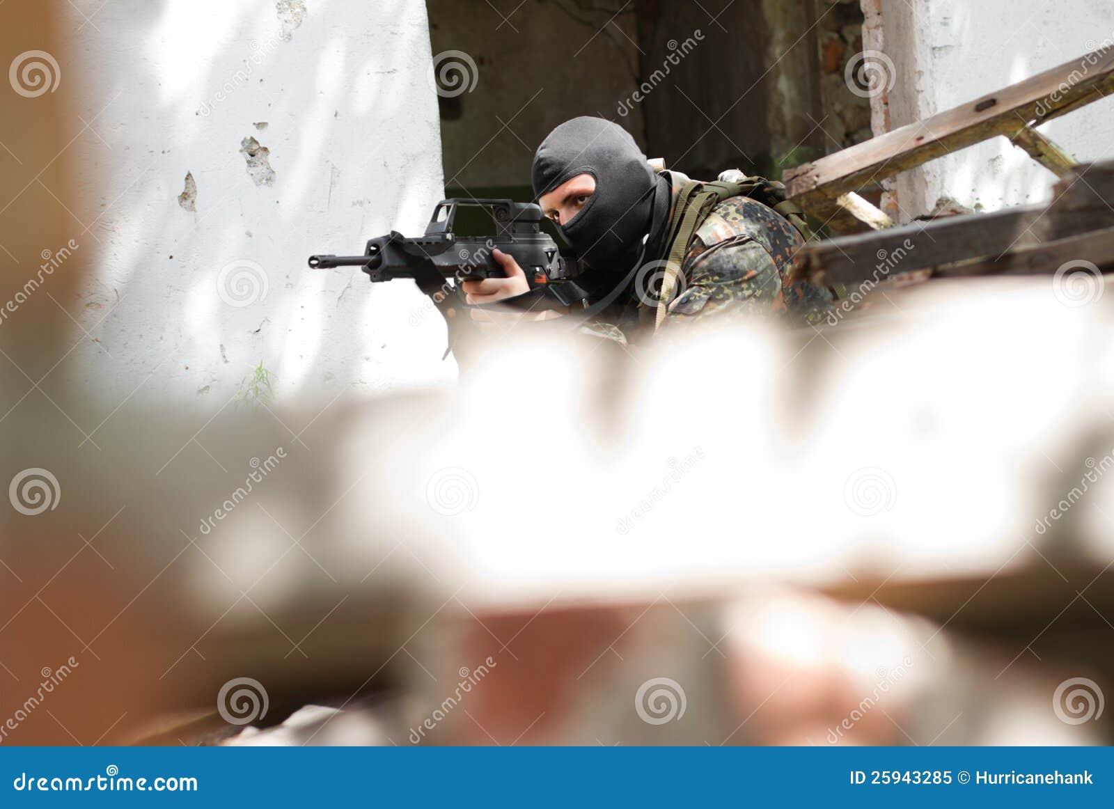 Terroriste dans le masque noir avec un canon