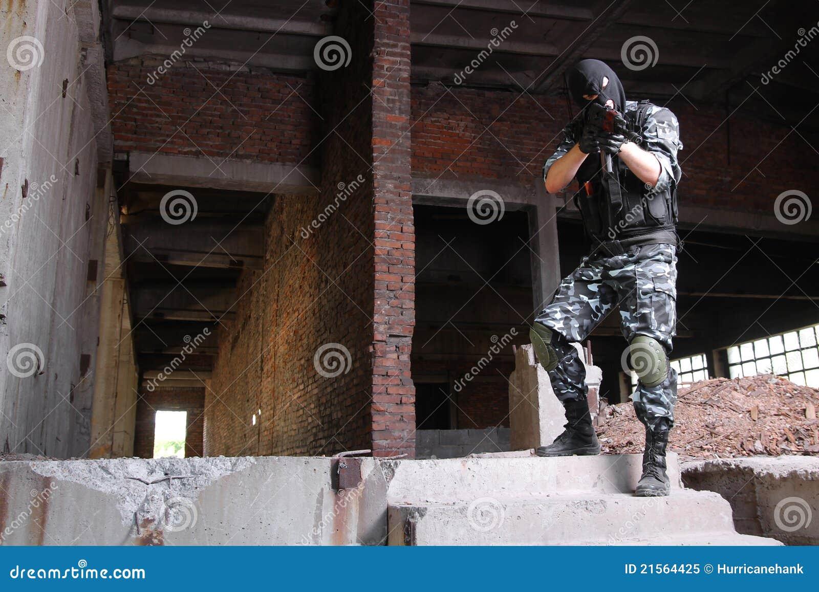 Terroriste dans le masque noir visant avec un canon