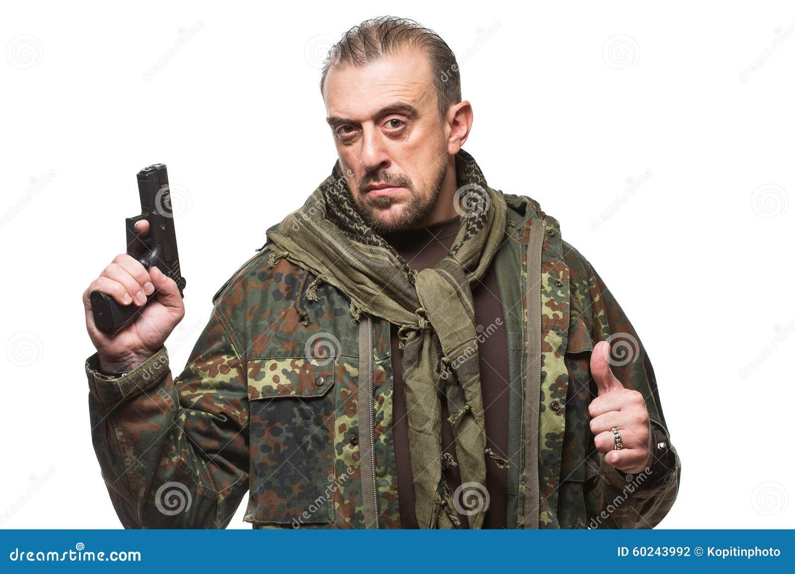 Terroriste masculin dans une veste militaire avec une arme à feu dedans